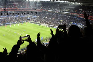 """Lyon's supporters cheer their team during the French L1 football match between Olympique Lyonnais (OL) and Troyes on January, 2016, at the """"Grand Stade"""" stadium in Decines-Charpieu, central-eastern France. AFP PHOTO / JEAN-PHILIPPE KSIAZEK"""